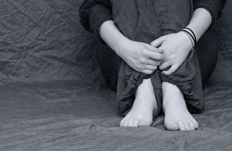 A person holding their knees tightly to their body while they are experiencing grief and loss