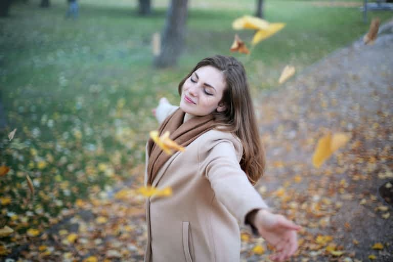 Woman with open arms while leaves are falling