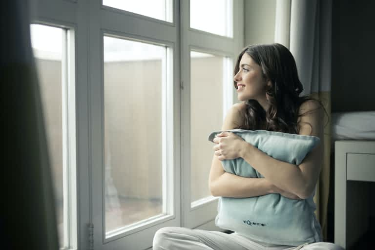 Dark haired woman hugging a pillowcase and smiling while looking out the window during her mental health day