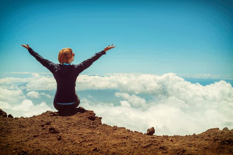 Person sitting on a cliff with both arms raised in gratitude