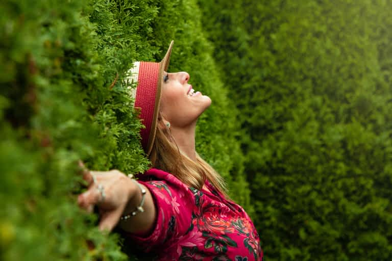 A woman with a hat leaning against tall bushes smiling