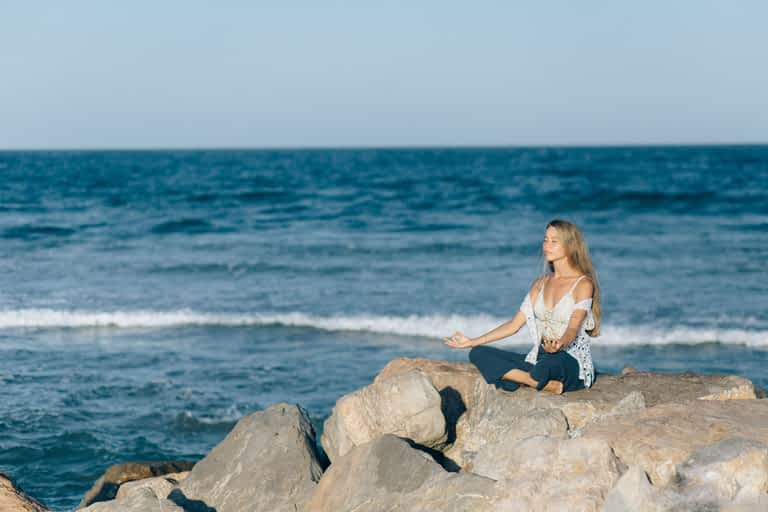 A woman meditating while sitting on rocks by the ocean