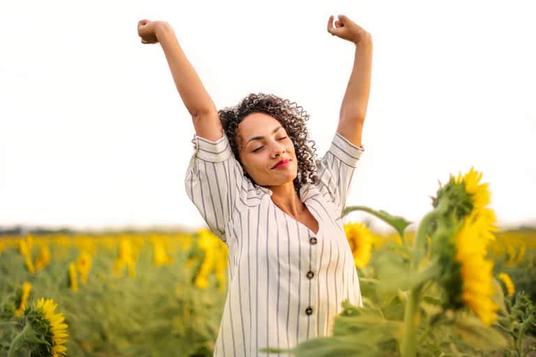 A woman raising her arms in the air with her eyes closed in a field of sunflowers