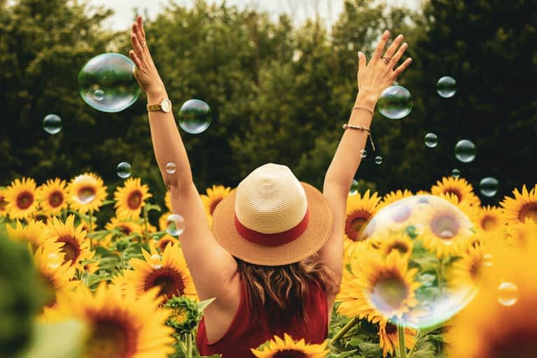A woman with her back turned raising her arms in a V shape while standing in a field of sunflowers