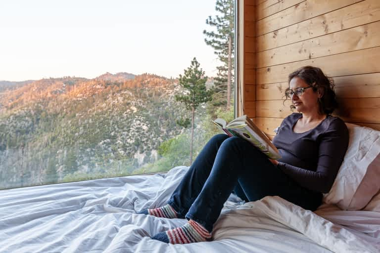 Getaway House Big Bear Pantea Rahimian sitting on the bed reading