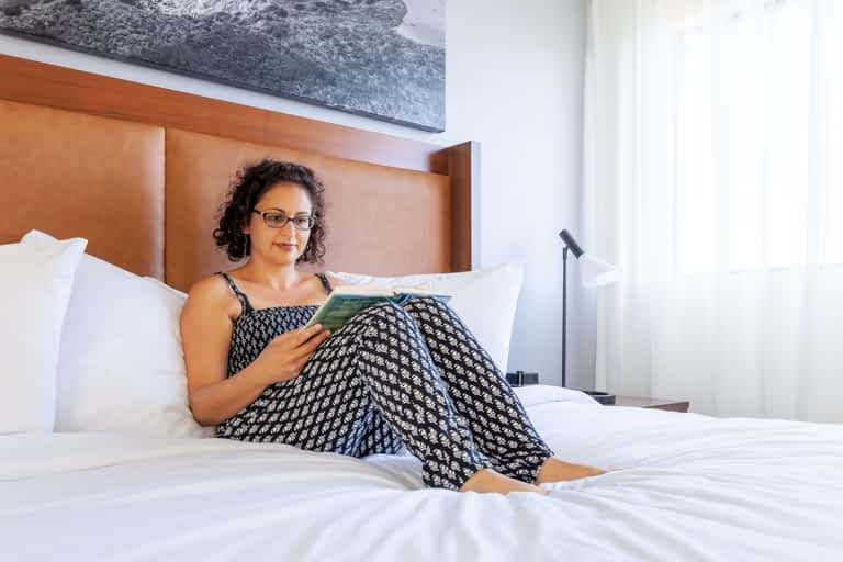 Pantea Rahimian sitting on a bed and reading