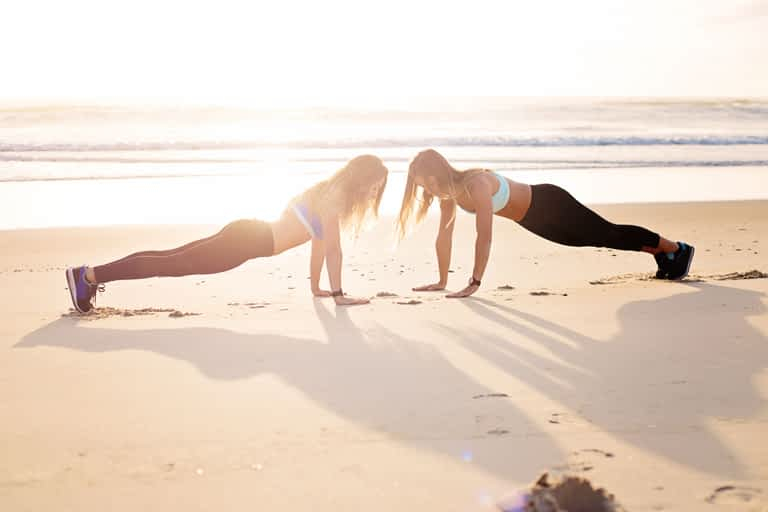 How to get motivated to work out in fall and winter with with two women on the beach in plank pose
